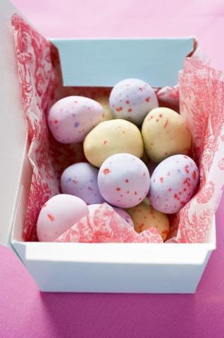 Umple o cutie mica de carton cu bomboane in forma de oua, invelita in servetele colorate