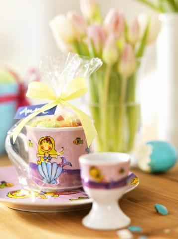 O cana deosebita de ceai plina cu bomboane, ambalata in celofan si legata cu funda
